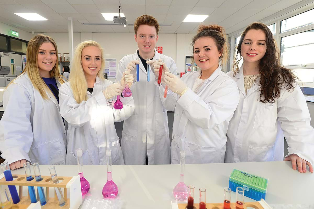 Photograph showing five science students carrying out an experiment