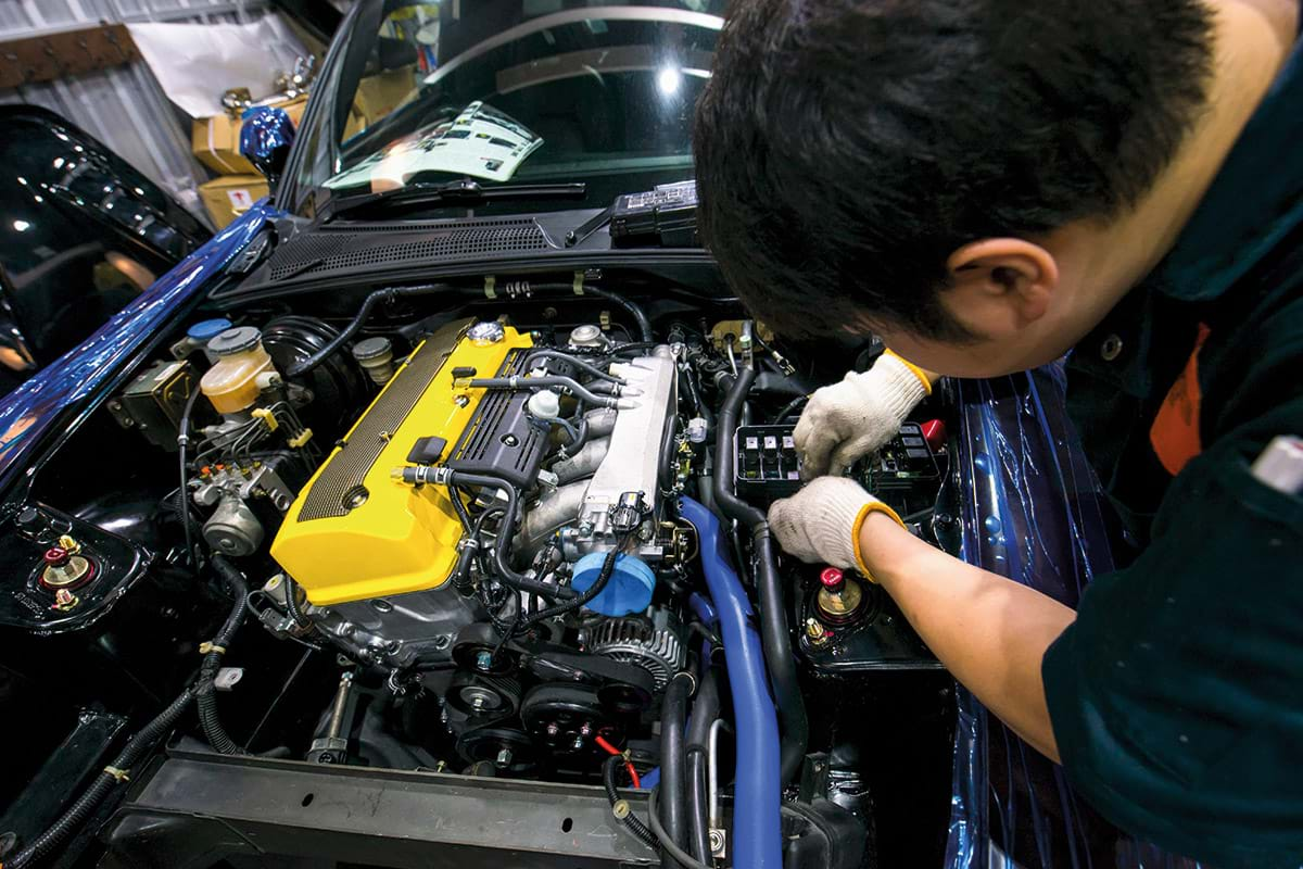 Photograph showing a student with his head down wearing gloves working on a car engine