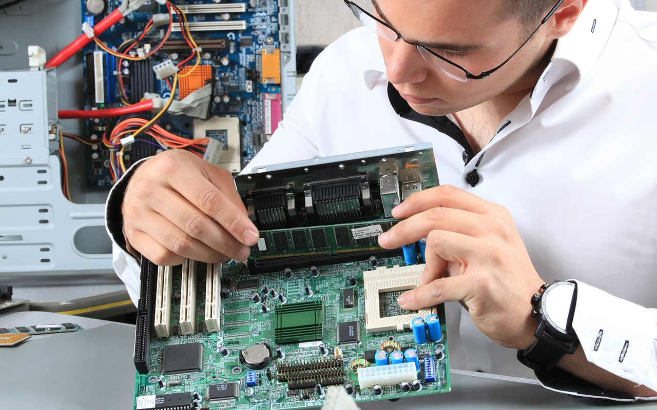 A photograph showing a student working at a mother board from inside a computer