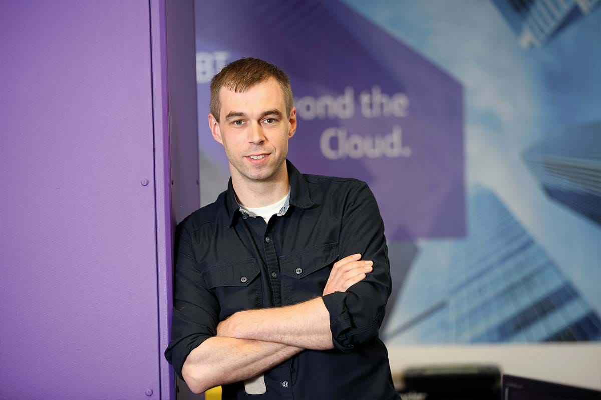 Photograph showing Patrick Garrett leaning against a purple wall at British Telecom