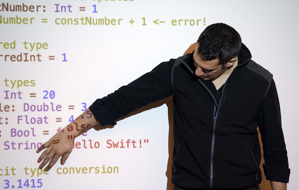 Male standing at the front of a room presenting computer code