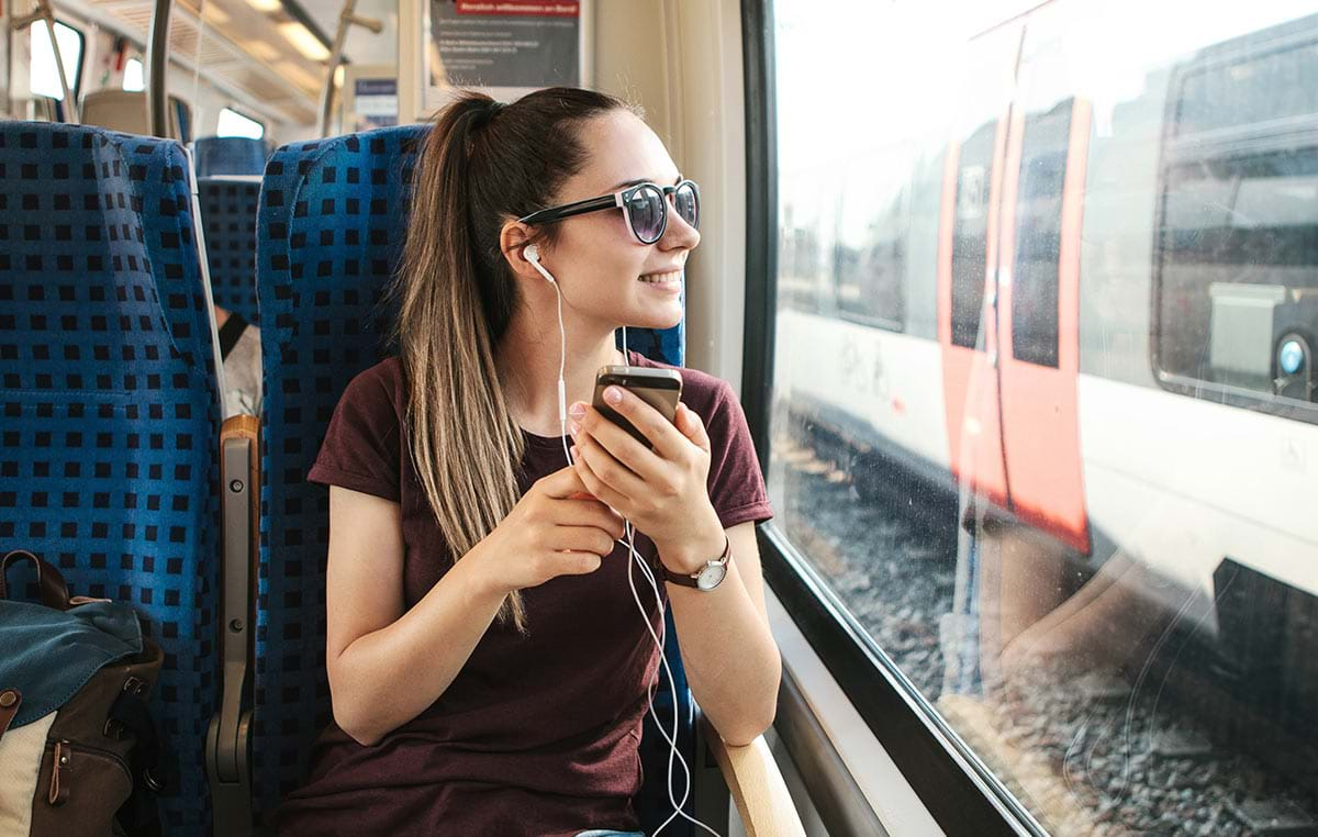Girl sitting on a train listening to music on her iPhone