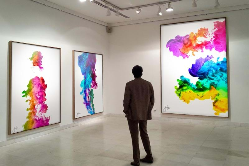 An image of a man standing in a gallery looking at the prints.